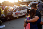 Luis Sone, right, and his girlfriend, Maritza Garcia, look at a vigil in front of Dallas police headquarters. Photo / AP