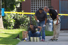 San Diego's Metro Arson Strike Team and SDPD homicide team gather evidence from the sidewalk and grassy area where a homeless person was attacked in downtown San Diego. Photo / AP