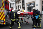 A victim of the shooting at the French satirical newspaper, Charlie Hebdo, is transported for treatment. Photo / File