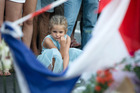 A young girl reacts as people lay flowers on La Promenade des Anglais' seafront in tribute to victims of the Nice terror attack. Photo / Getty Images