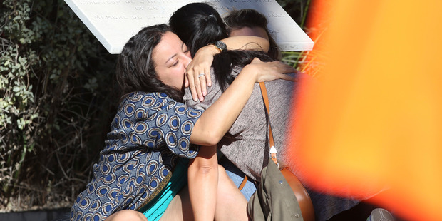 Parents of victims embrace each other near the scene. Photo / AP