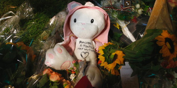 A teddy bear sits between flowers at a makeshift memorial in Nice. Photo / AP