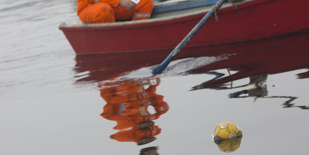 Oil workers row a boat near a ball floating in Guanabara bay during a protest against the pollution of the bay, in Rio de Janeiro, Brazil. Photo / AP