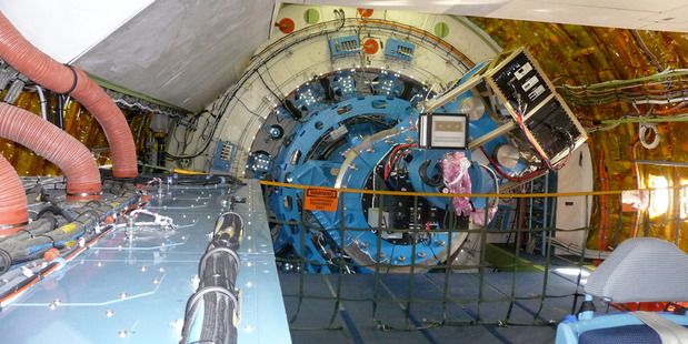 A view looking tailward through the cabin of NASA's SOFIA flying observatory. At the back, two science instruments jut from a bulkhead. Photo / Mike Wall / Space.com