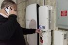 A customer inspects a Tesla Motors powerwall unit inside a home. Photo / Ian Thomas Jansen-Lonnquist