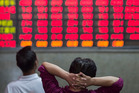 Investors look at an electronic board displaying share prices at a securities exchange house in Shanghai, China. Photo / Bloomberg