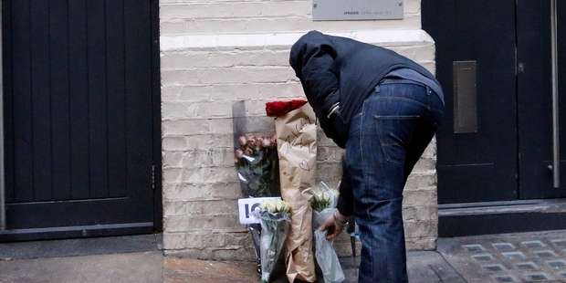 A man places flowers at his birthplace at Brixton in London.  Photo / AP
