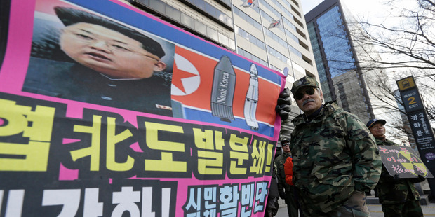 A banner shows a picture of North Korean leader Kim Jong Un as South Korean war veterans stage a rally against North Korea in Seoul. Photo / AP