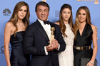 Sylvester Stallone holds his Golden Globes trophy for best performance by an actor in a supporting role alongside Sophia Stallone, Scarlet Stallone and Sistine Stallone. Photo/AP