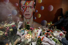 People gather next to tributes placed near a mural of British singer David Bowie by artist Jimmy C, in Brixton, south London. Photo/AP