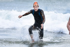 Andrew Lloyd reaches the beach ahead of the finish of Sunday's Round the Mount swim. Photo / George Novak