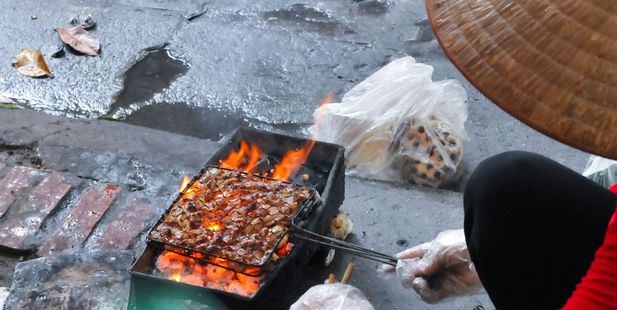A woman cooks barbecue meat on the streets of Hanoi in Vietnam. Photo / 123RF