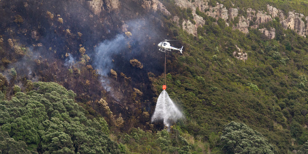 Helicopters use monsoon buckets to drop water on the remains of a bush fire that took hold near the summit of Mt Maunganui. Photo / Alan Gibson