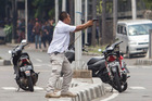 A plainclothes police officer aims his gun at attackers during a gun battle following explosions in Jakarta. Photo / AP