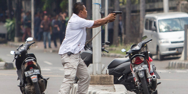 Loading A plainclothes police officer aims his gun at attackers during a gun battle following explosions in Jakarta. Photo / AP