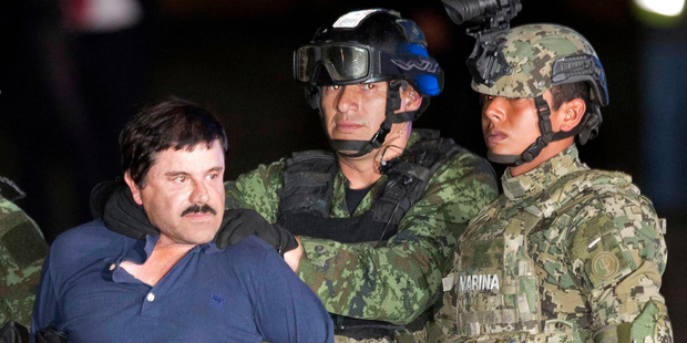 Guzman is made to face the press as he is escorted to a helicopter in handcuffs by Mexican soldiers and marines . Photo / AP