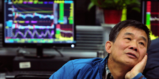 A man looks at stock prices at a brokerage house in Jiujiang in central China's Jiangxi province. Photo / AP
