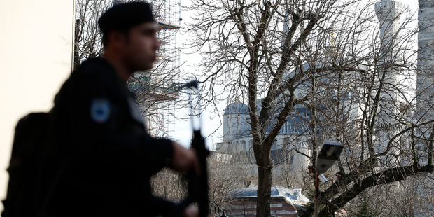 A policemen patrols at the Sultanahmet district after an explosion as the Blue Mosque is seen in the background in Istanbul. Photo / AP