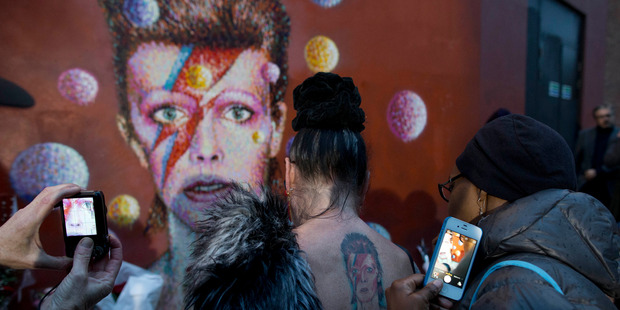 Fans pay tribute to David Bowie at a mural by artist Jimmy C in Brixton, south London. Photo / AP