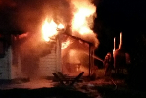Flames shoot from Ngaere Ututaonga's home on Monday night.