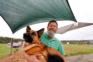 Tony Gill and dog Tica are happy to see stolen shade sails returned to Pohe Island's dog park. Photo / John Stone