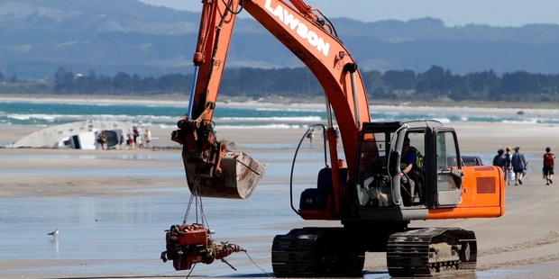 A digger, owned by Lawson Cartage, carries the engine from the stricken yacht P.Lee Can on to a truck on Ruakaka Beach. Photo / John Stone