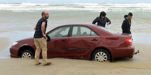 Mahmoud Helal , Ali Ibrahim and Hassan Almulla with one of their 3 cars stuck in sand on Tomahawk beach. Photo / Otago Daily Times