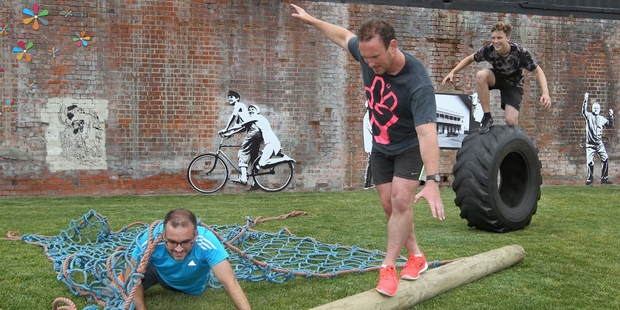 Aspyre Fitness owner Jamie Loughran tests his balance as gym member Nick Stygall (left) and Aspyre staff member Jacob McNeil practise their training techniques for the urban obstacle race.