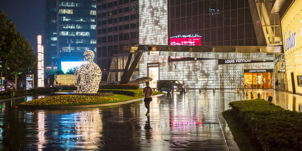 A pedestrian holding an umbrella walks past a Louis Vuitton store in Shanghai in October. Photo / Bloomberg