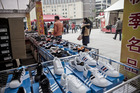 Shoppers walk past a stall selling discounted sneakers in Shanghai. Photo / Bloomberg
