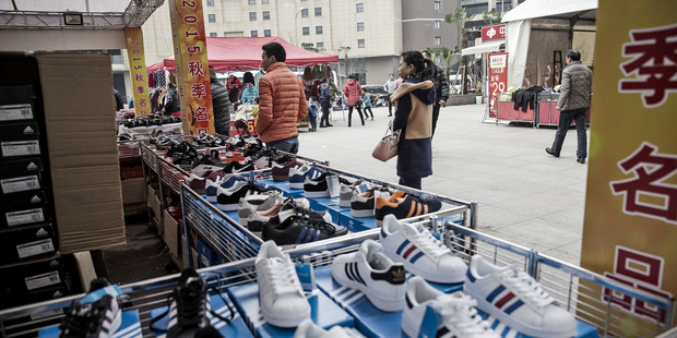 Loading Shoppers walk past a stall selling discounted sneakers in Shanghai. Photo / Bloomberg