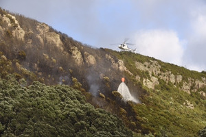 Two helicopters dump massive buckets of water on the fire on the eastern side of Mauao. Photo/George Novak