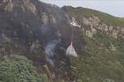 Helicopters continue to battle the scrub fire on the eastern side of Mount Maunganui this morning.