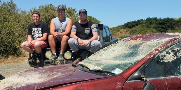 Inspecting the car they helped salvage from a Dunedin beach are (from left) Rhys McAlevey (24), Ossian Woods (18) and Blake Stanley (20). Photos by Stephen Jaquiery & supplied.