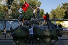 Citizens stand on a damaged armoured personnel carrier attacked by protesters near the Turkish military headquarters in Ankara. Photo / AP