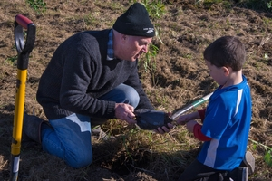 Ronan McDonald, an Omakere pupil,  helps principal George McGowan remove a seedling for planting. Photo / Lauren Buchholz