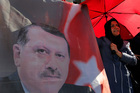 A Turkish woman stands next to a portrait of Turkish President Recep Tayyip Erdogan during a protest against the military coup outside Turkey's Parliament in Ankara. Photo / AP