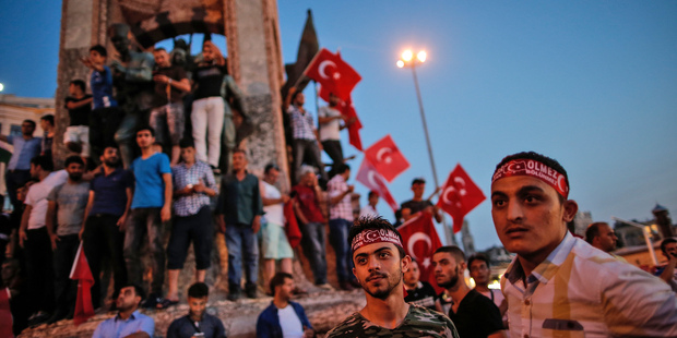 People wave Turkish flags as they gather at a pro-government rally in central Istanbul's Taksim Square. Photo / AP