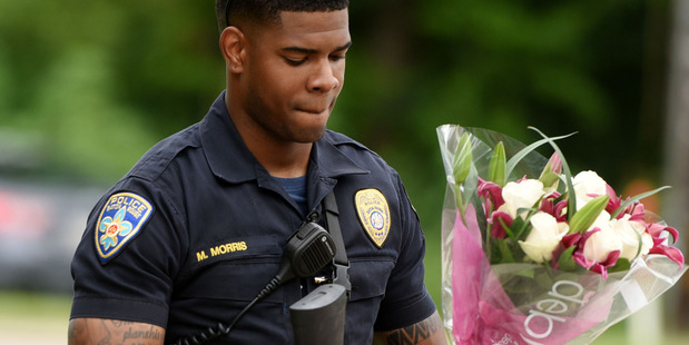 Baton Rouge Police Department Officer Markell Morris holds a bouquet of flowers and a Superman figure that a citizen left at the hospital where the officers were brought to. Photo / AP