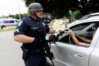Baton Rouge police officer Randy Bonaventure takes a bouquet of flowers at the Our Lady of the Lake Hospital where the police officers were brought today. Photo / AP