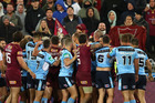 Players from both the NSW Blues and Queensland Maroons wrestle during game three of State Of Origin. Photo / Getty