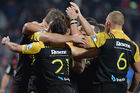Callum Gibbins of the Hurricanes celebrates with team mates after scoring a try against the Crusaders. Photo / Getty