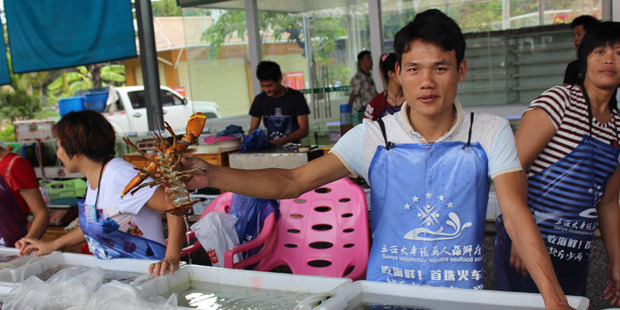 A fish vendor with a live crayfish at the Ten Thousand People open-air dining facility in Sanya City on Hainan Island, China. Photo / Barbara Boyce