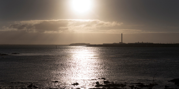 Loading The sun rising over the Tiwai Point Aluminium Smelter viewed from Bluff. Photo / Mark Mitchell
