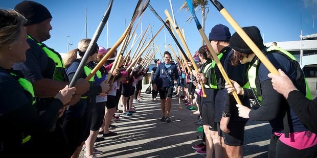 The police staff torch relay - Police officer Gaylene McFarlane takes the torch through a guard of honour after paddling across Pilot Bay in a waka. PHOTO/ANDREW WARNER