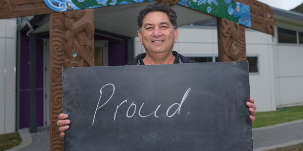 Campbell Dewes, 54, at Hicks Bay with a chalkboard message on what it means to be a New Zealander. Photo / Mark Mitchell