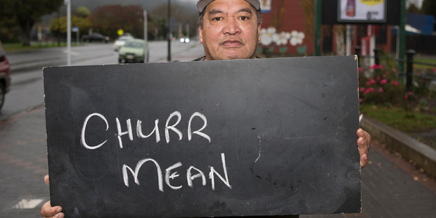 Frank Tahana in Ngaruawahia with a chalkboard message on what it means to be a New Zealander. Photo / Mark Mitchell