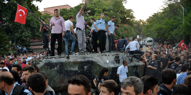People gather and some stand atop of a Turkish army, armoured vehicle in Ankara. Photo / AP