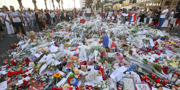 People gather at a makeshift memorial to honour the victims of the Nice attack. Photo / AP