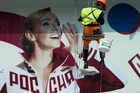 A municipal worker cleans a shop window of a display with a portrait of Russia's Olympic champion Tatyana Navka dressed in a Russian Olympic National team uniform in Moscow. Photo / AP